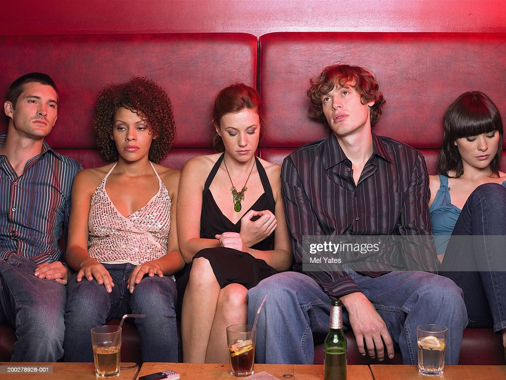Group of five friends sitting in row on banquette with drinks : Stock Photo