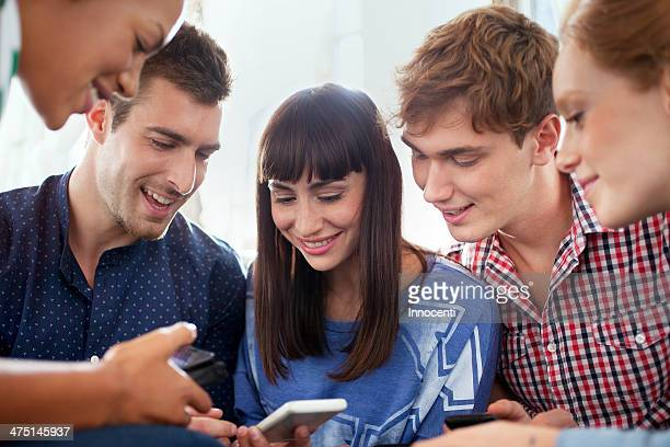 Group of five friends using smartphones