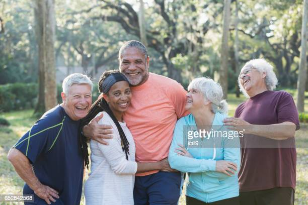Group of five multi-ethnic seniors standing in park