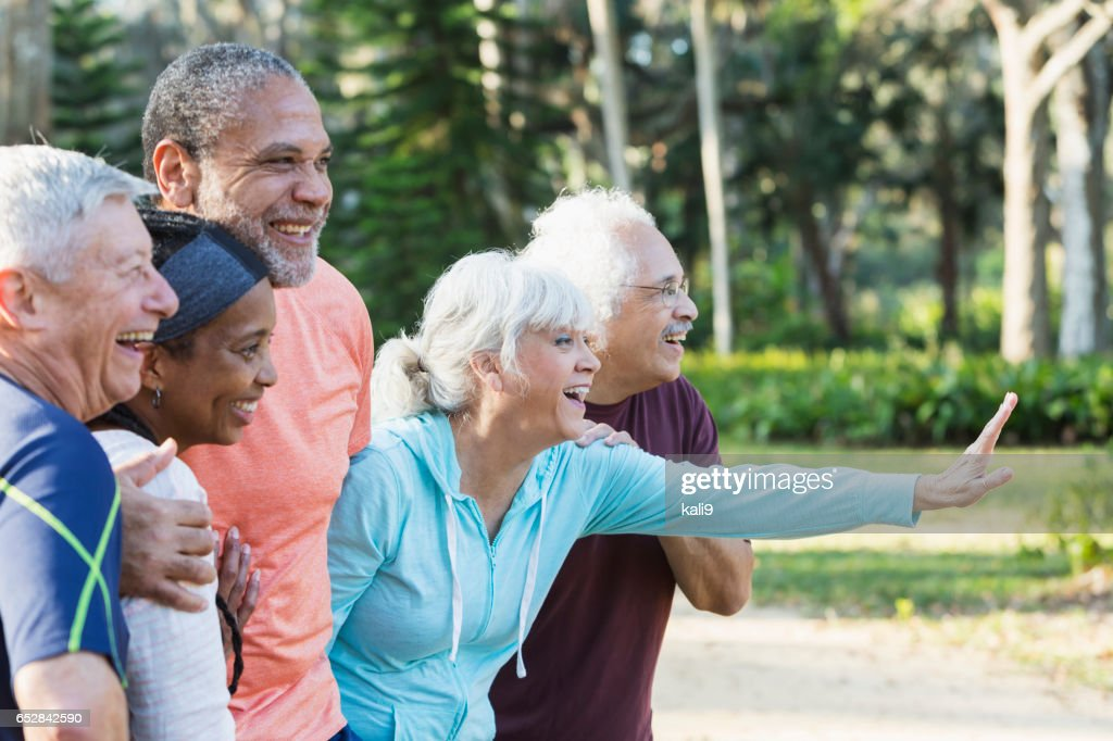 Group of five multi-ethnic seniors standing in park : Stock Photo