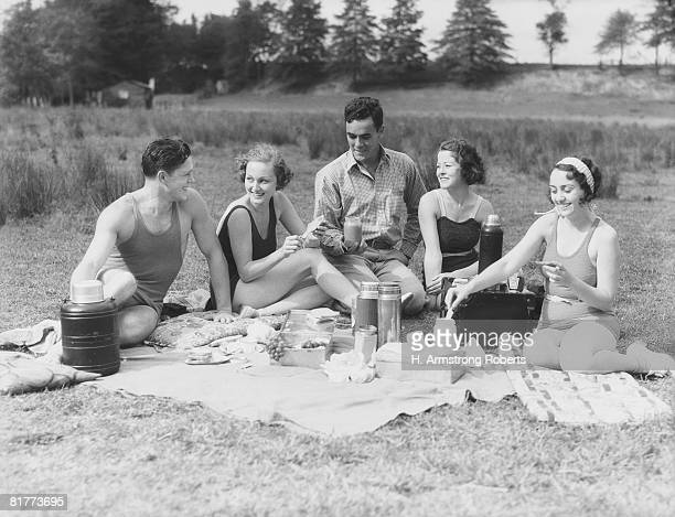 Group of five people having summer picnic on beach.