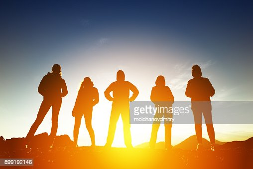 Group of five peoples in silhouettes at sunset : Stock Photo