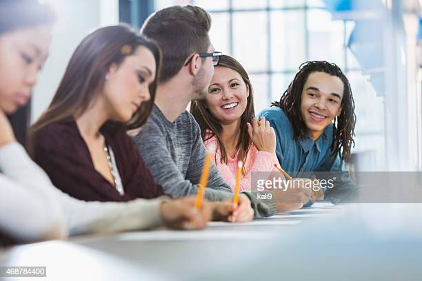 Group of five teenagers in a row, writing