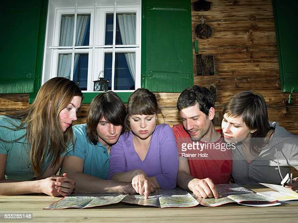 Group of Five Young People Looking Together at Map