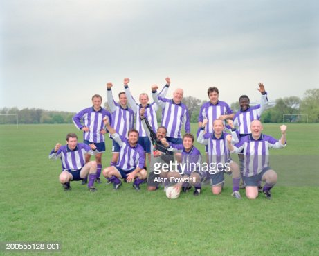 Group of football players posing and cheering, portrait