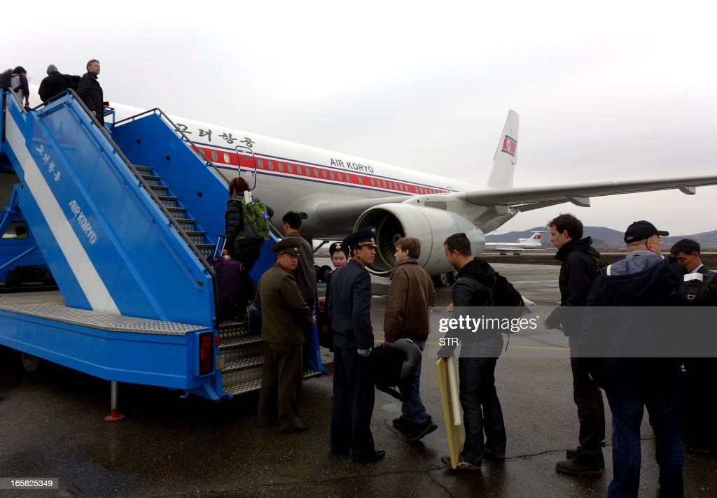 A group of foreign diplomats and tourists board an Air Koryo flight to Beijing at the airport in Pyongyang, North Korea on April 6, 2013. Foreign diplomats in North Korea appeared to be staying put, ignoring a warning by Pyongyang that they should consider evacuating their missions amid soaring nuclear tensions, as Pyongyang had informed embassies it could not guarantee their safety if a conflict broke out as concerns grew that the isolated state was preparing a missile launch.