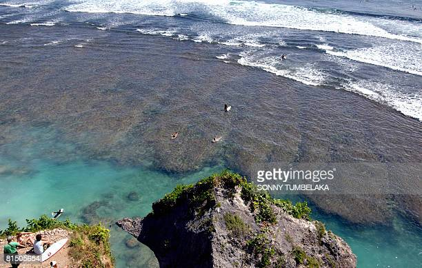 A group of foreign tourists rest as other head to surf at the Uluwatu beach in Jimbaran on the resort island of Bali on June 4 2008 The number of...