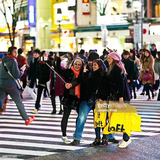 A group of foreigners visiting Japan take photo with a selfie stick at the scramble crossing in Shibuya