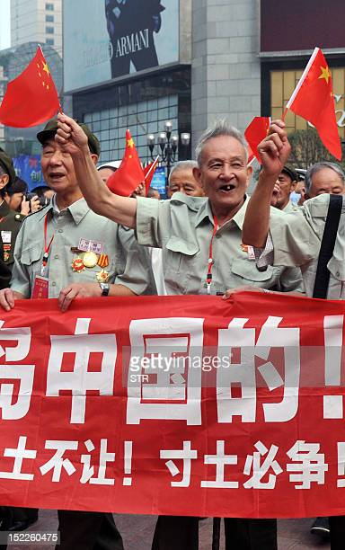 A group of former Chinese soldiers in the Korean War carry Chinese national flags and shout slogans during a protest in Chongqing against Japan's...