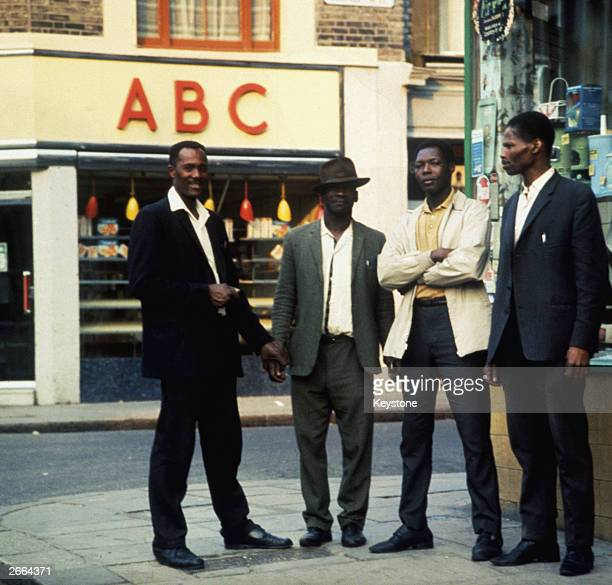 A group of four AfroCaribbean men stand on a street corner in Notting Hill London