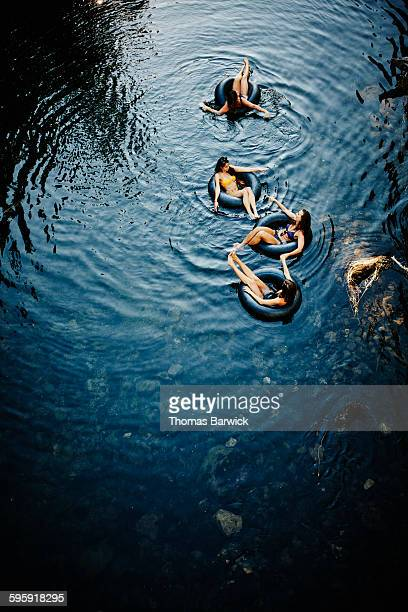 Group of four female friends floating on river