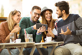 Group of four friends having a coffee together. Two women and two men at cafe talking laughing and enjoying their time using digital tablet.