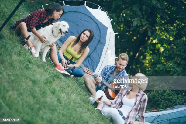 Groupe de quatre amis sur le camping en forêt