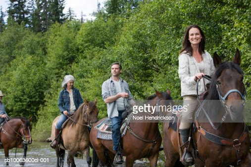 Group of four horse riders crossing river, woman looking at camera