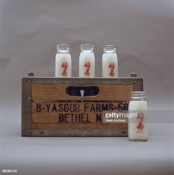 A group of four milk bottles and a wooden milk crates stamped with the name of Yasgur Farms New York 2009 Yasgur Farms in Bethel New York was the...