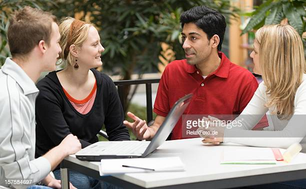 Group of four multi-ethnic students in teamwork with laptop presentation