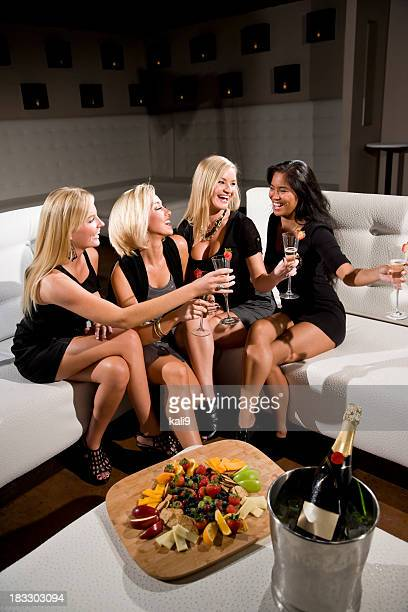 Group of four young women with champagne glasses