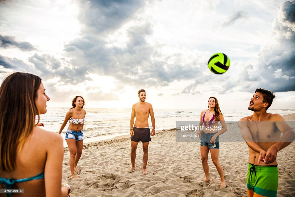 Group of friend play volley on the beach