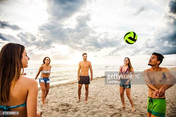 Grupo de amigos Juegue al voleibol en la playa