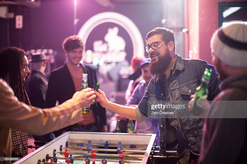 Group of friends and table football game in bar