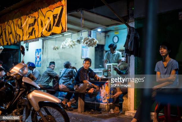 A 'WARKOP' IN SURABAYA EAST JAVA SURABAYA SUARABAYA INDONESIA A group of friends are seen drinking tea in a Warkop during the night 'Warkop' is the...
