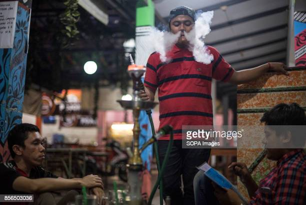 A 'WARKOP' IN SURABAYA EAST JAVA SURABAYA INDONESIA A group of friends are seen smoking shisha in a Warkop during the night 'Warkop' is the name of...