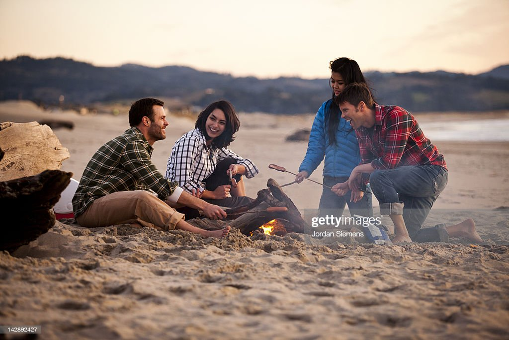 Group of friends around a camp fire. : Stock Photo