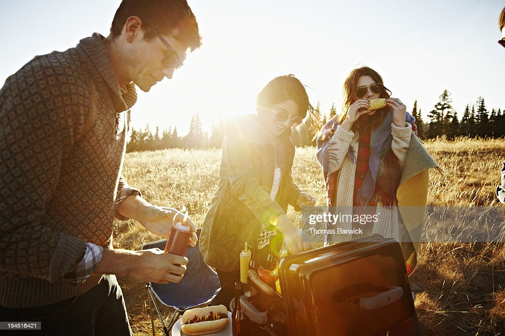 Group of friends around barbecue eating food : Stock Photo