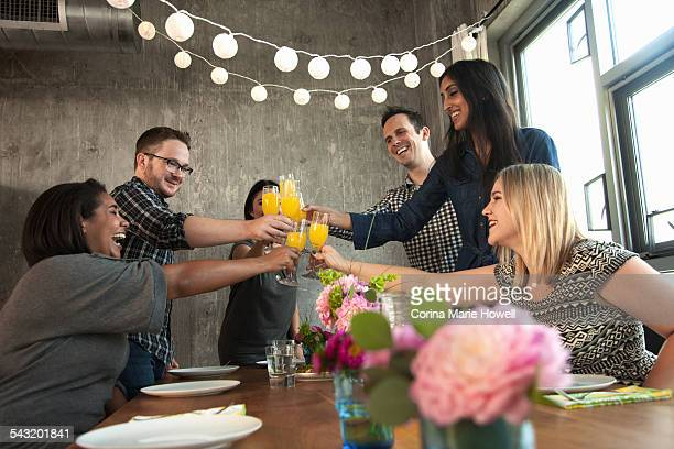 Group of friends around table, raising glasses, making toast