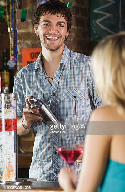 Group of friends at bar, focus on man holding bottle