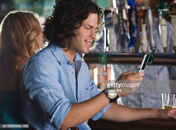 Group of friends at bar, focus on man using mobile phone