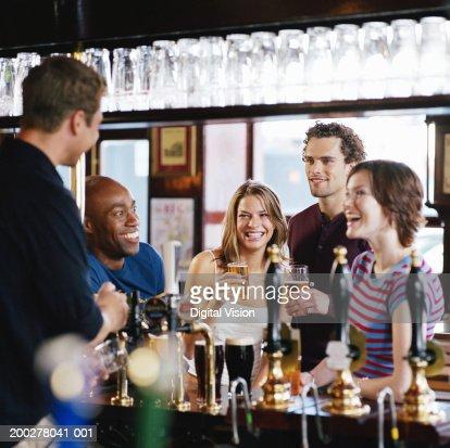 Group of friends at bar talking to barman, smiling : Stock Photo