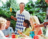 Group of friends at lunch table outdoors, man holding corn cob