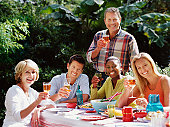 Group of friends at lunch table outdoors, smiling, portrait