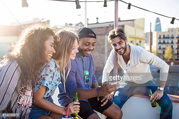 Group of friends at rooftop party using mobile phone