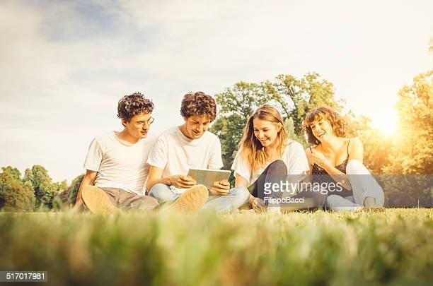 Gruppe von Freunden im park zusammen mit einem Tablet
