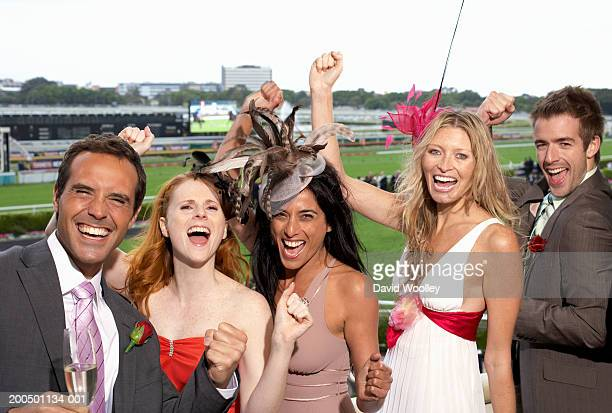 Group of friends at the races, cheering, portrait