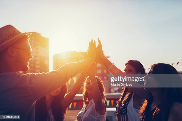 Group of friends at the rooftop doing high five