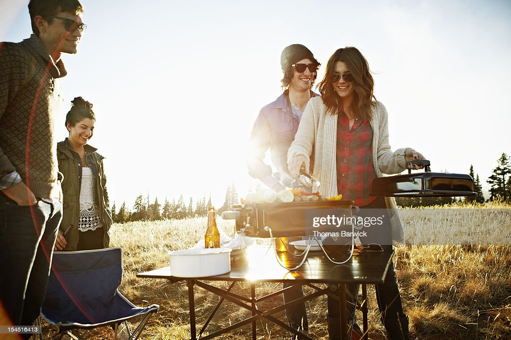Group of friends barbecuing in field at sunset