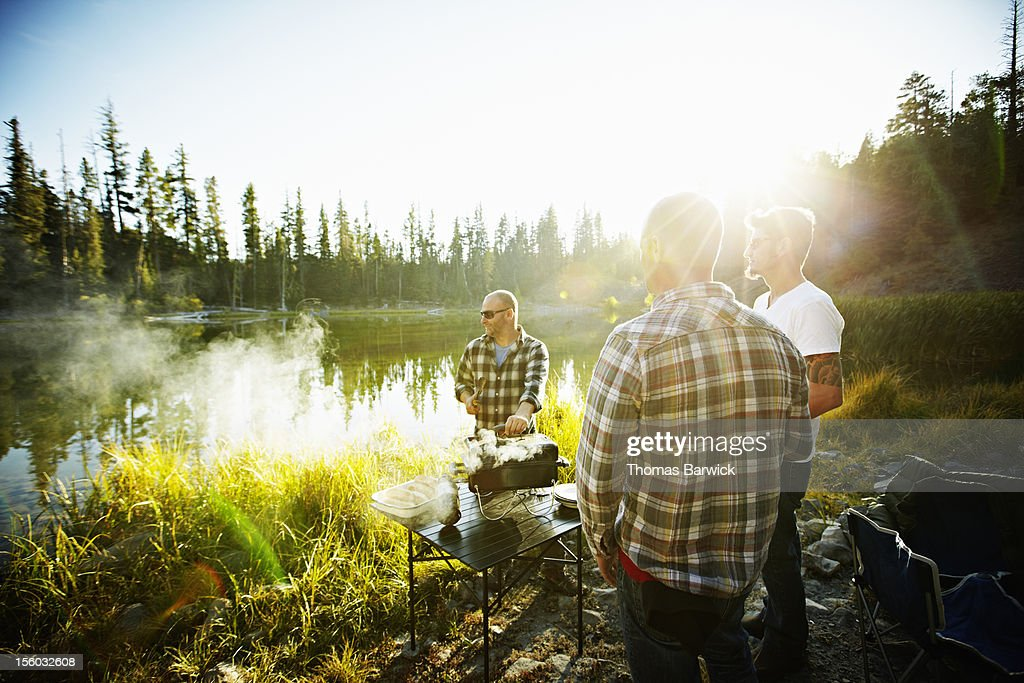 Group of friends barbecuing next to mountain lake : Stock Photo