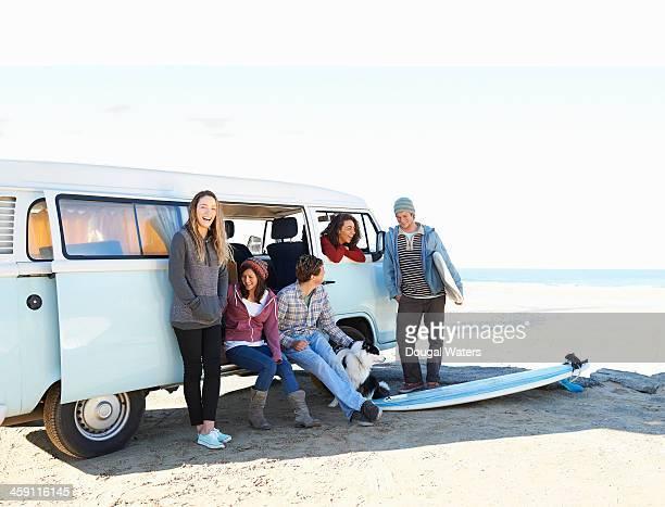 Group of friends beside camper van.