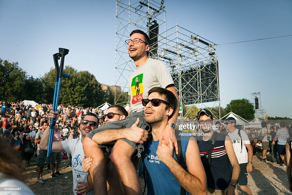 A group of friends brings an injured friend on them shoulders to the Rolling Stones show in Rome at Circus Maximus