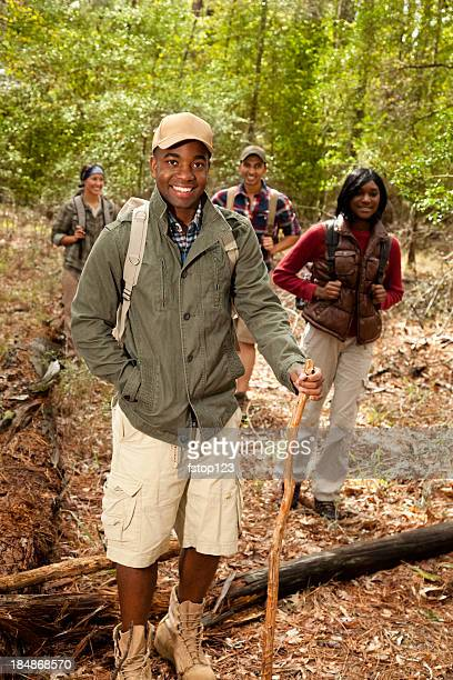 Group of friends camping, hiking in woods, forest. African descent.
