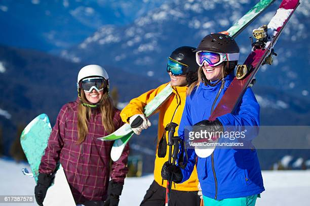 Group of friends carrying ski and snowboard gear.