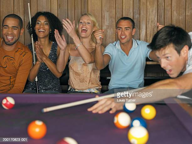 Group of friends cheering and applauding man playing pool
