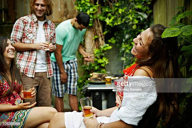 Group of friends cooking at barbecue laughing