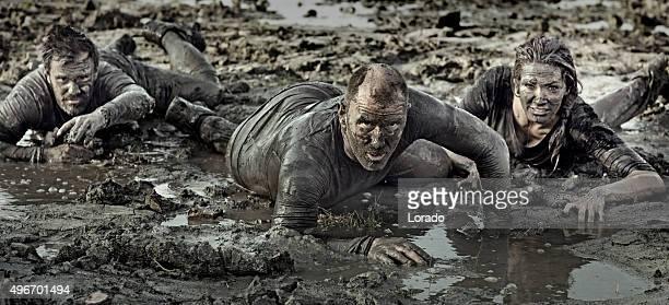 Groupe d'amis de ramper dans la boue