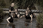 group of friends crossing canal during mud run