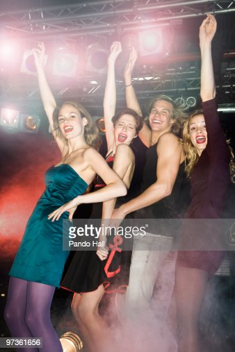 Group of friends dancing and laughing in nightclub : Stock Photo