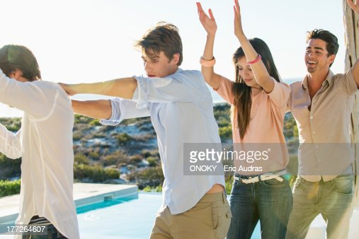 Group of friends dancing at the poolside : Stock Photo